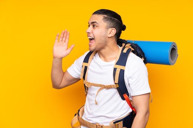 Jonge bergbeklimmer aziatische man met een grote rugzak geïsoleerd op geel schreeuwen met wijd open mond