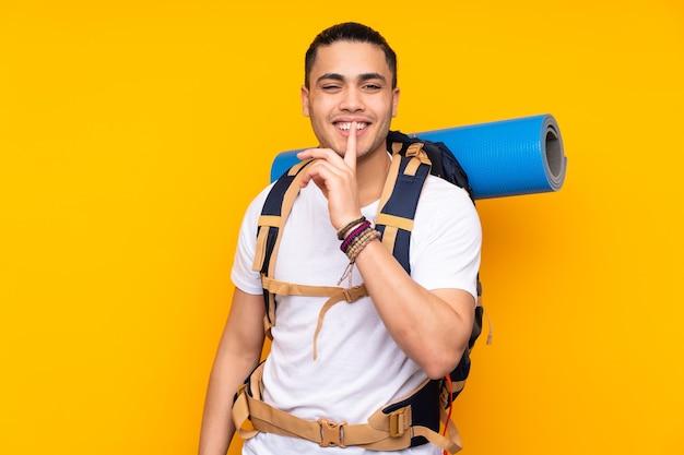 Jonge bergbeklimmer aziatische man met een grote rugzak geïsoleerd op geel stilte gebaar doen