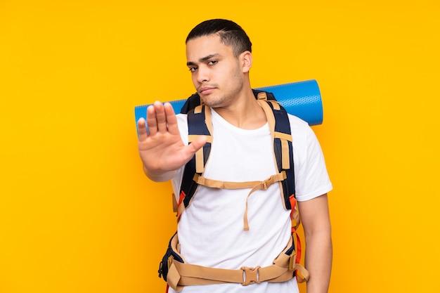Jonge bergbeklimmer aziatische man met een grote rugzak geïsoleerd op geel stop gebaar met haar hand maken
