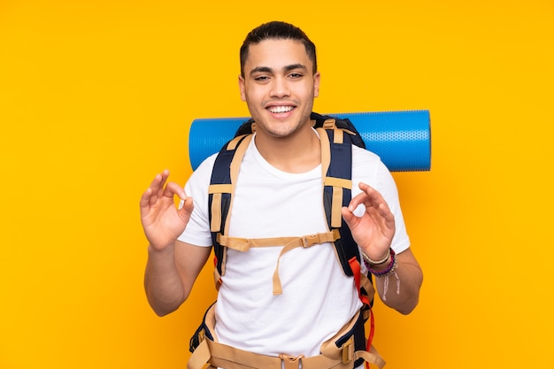 Jonge bergbeklimmer aziatische man met een grote rugzak geïsoleerd op gele achtergrond met een ok teken met vingers