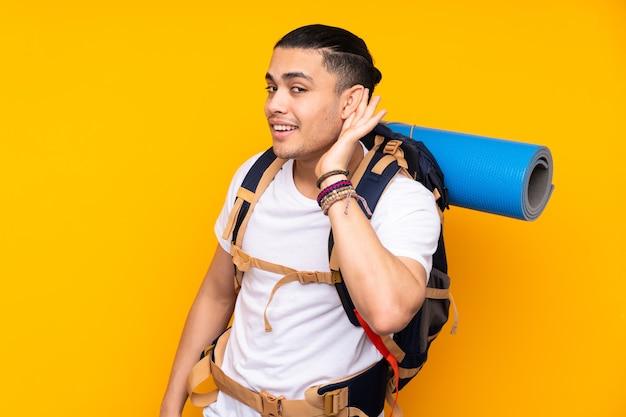 Jonge bergbeklimmer aziatische man met een grote rugzak geïsoleerd op gele muur iets te luisteren
