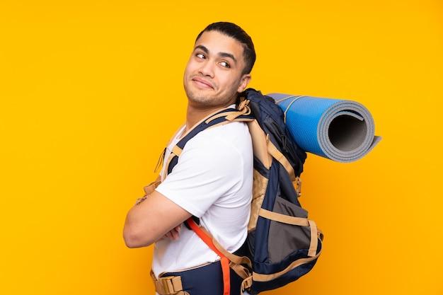 Jonge bergbeklimmer aziatische man met een grote rugzak geïsoleerd op gele muur lachen