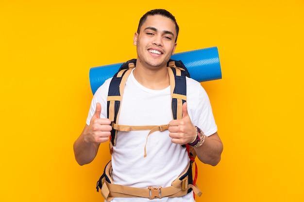 Jonge bergbeklimmer aziatische man met een grote rugzak geïsoleerd op gele muur met een duim omhoog gebaar