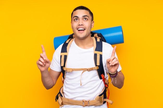 Jonge bergbeklimmer aziatische man met een grote rugzak geïsoleerd op gele muur wijzend met de wijsvinger een geweldig idee