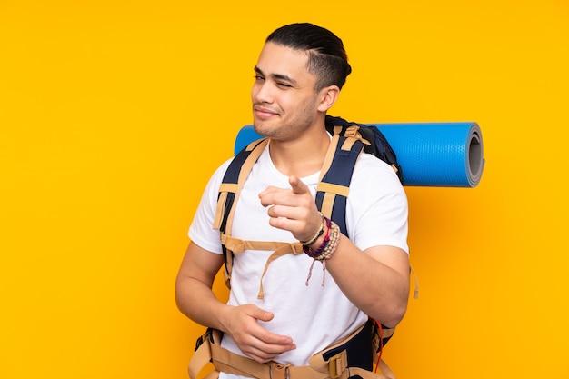 Jonge bergbeklimmer aziatische man met een grote rugzak geïsoleerd op gele punten vinger naar je