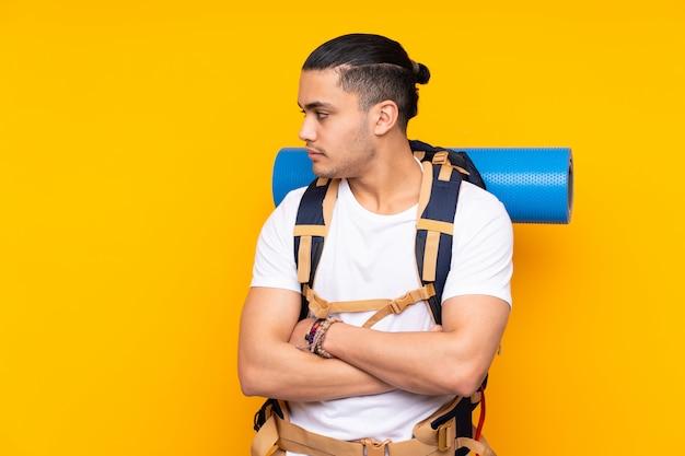 Jonge bergbeklimmer aziatische mens die met een grote rugzak op gele muur kant kijken
