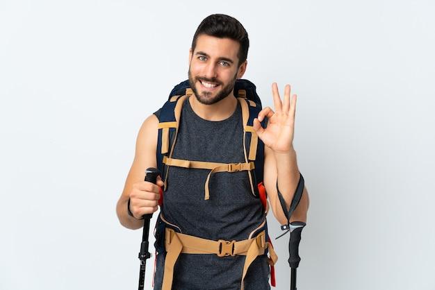Jonge bergbeklimmer man met een grote rugzak en wandelstokken geïsoleerd op een witte muur met een ok teken met vingers