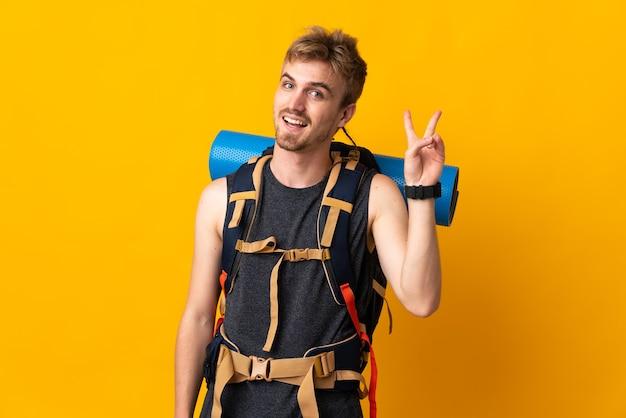 Jonge bergbeklimmer man met een grote rugzak geïsoleerd glimlachend en overwinningsteken tonen