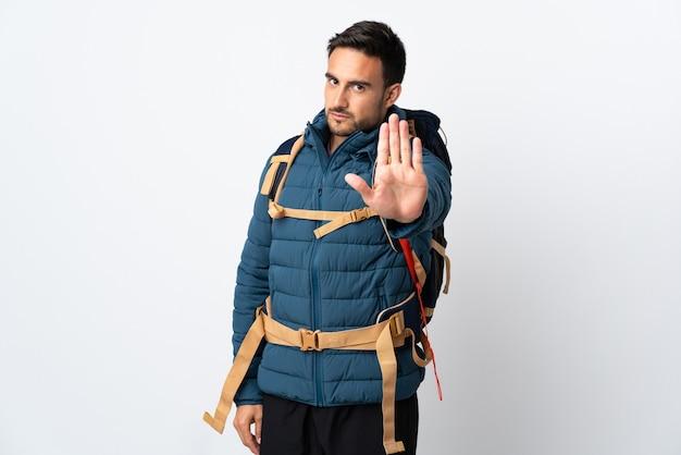 Jonge bergbeklimmer man met een grote rugzak geïsoleerd op een witte achtergrond stop gebaar met haar hand maken