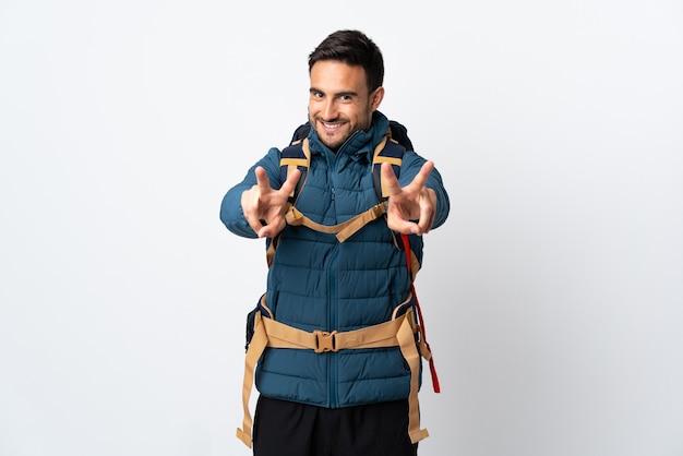 Jonge bergbeklimmer man met een grote rugzak geïsoleerd op een witte muur glimlachend en overwinningsteken tonen