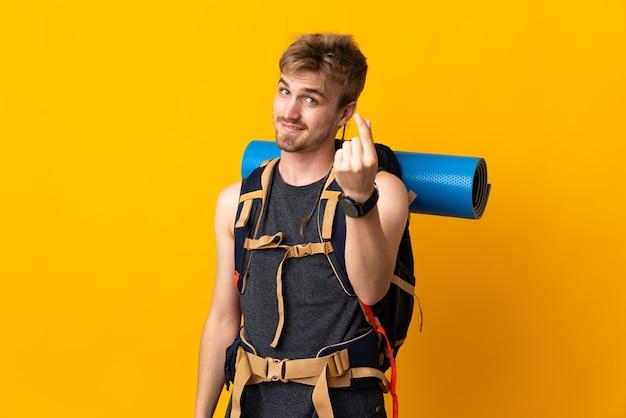 Jonge bergbeklimmer man met een grote rugzak geïsoleerd op gele muur geld gebaar maken