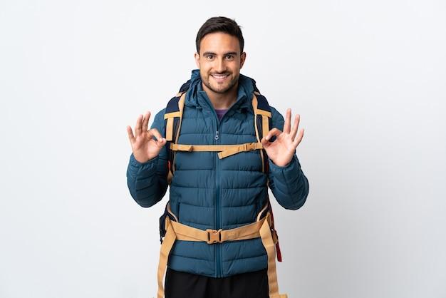 Jonge bergbeklimmer man met een grote rugzak geïsoleerd op wit met een ok teken met vingers
