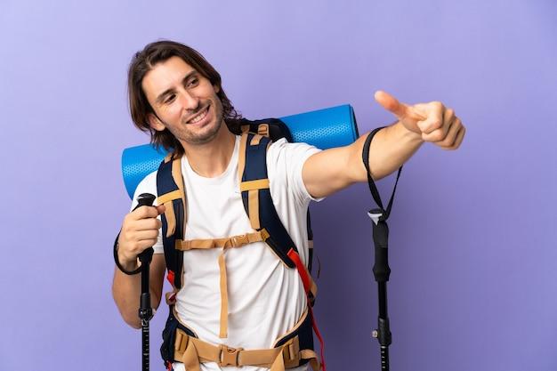 Jonge bergbeklimmer man met een grote rugzak met een duim omhoog gebaar