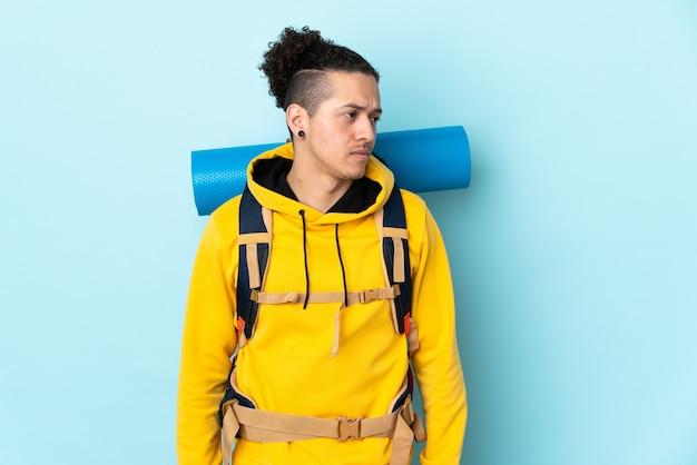 Jonge bergbeklimmer man met een grote rugzak over geïsoleerde blauw uitziende kant