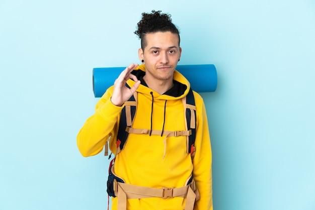 Jonge bergbeklimmer man met een grote rugzak over geïsoleerde blauwe achtergrond met een ok teken met vingers