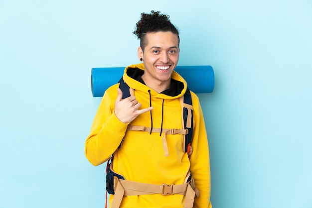 Jonge bergbeklimmer man met een grote rugzak over geïsoleerde blauwe achtergrond telefoongebaar maken