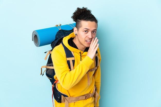 Jonge bergbeklimmer man met een grote rugzak over geïsoleerde blauwe iets fluisteren