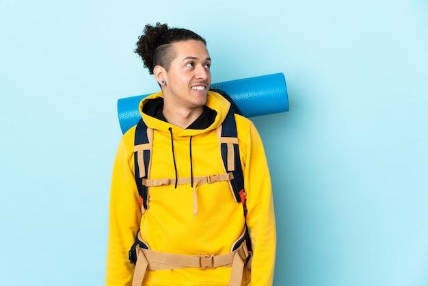 Jonge bergbeklimmer man met een grote rugzak over geïsoleerde blauwe lachen en kijken