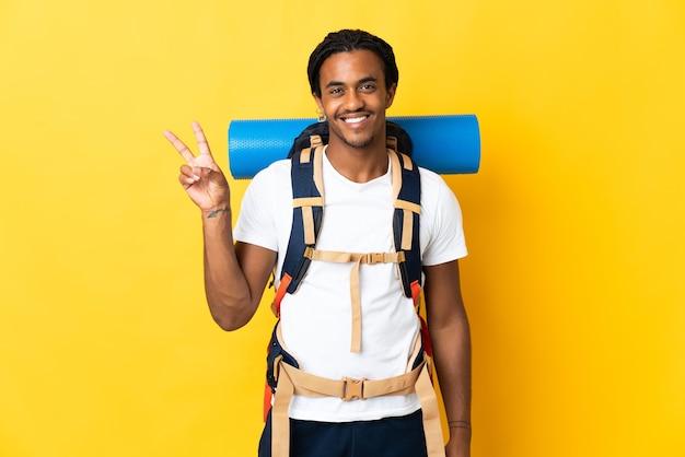 Jonge bergbeklimmer man met vlechten met een grote rugzak geïsoleerd op gele achtergrond glimlachend en overwinningsteken tonen
