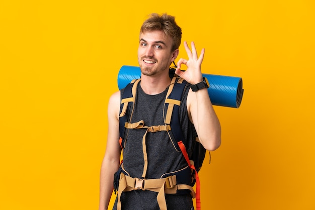 Jonge bergbeklimmer met een grote rugzak die op gele achtergrond wordt geïsoleerd die ok teken met vingers toont