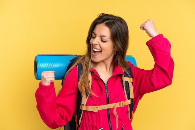 Jonge bergbeklimmer met een grote rugzak geïsoleerd op een gele achtergrond die een overwinning viert