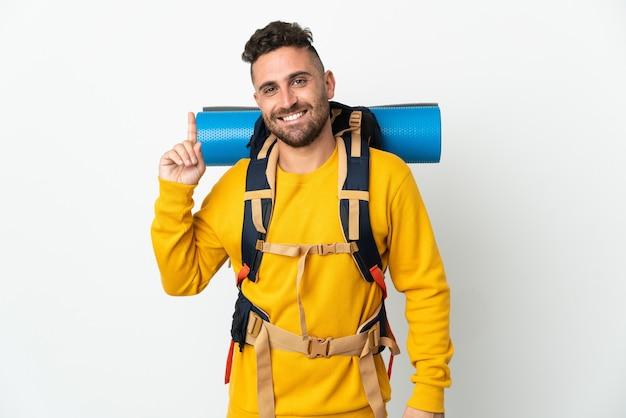 Jonge bergbeklimmer met een grote rugzak over een geïsoleerde achtergrond die een vinger toont en opheft als teken van het beste