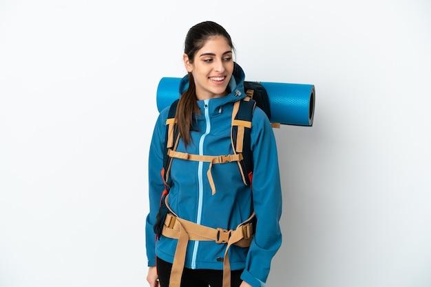 Jonge bergbeklimmer met een grote rugzak over een geïsoleerde achtergrond die naar de zijkant kijkt en glimlacht