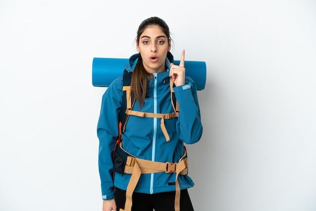 Jonge bergbeklimmer met een grote rugzak over een geïsoleerde achtergrond die van plan is de oplossing te realiseren terwijl hij een vinger opsteekt