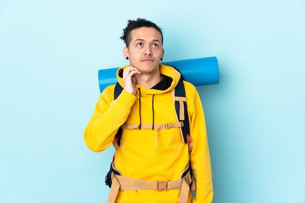 Jonge bergbeklimmer met een grote rugzak over geïsoleerd blauw die een idee denken