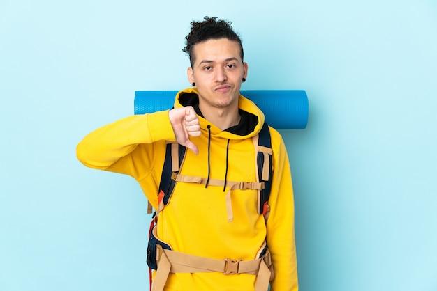 Jonge bergbeklimmer met een grote rugzak over geïsoleerd blauw met duim omlaag teken
