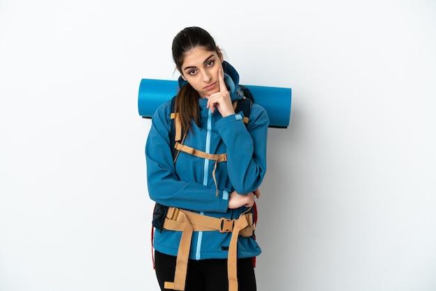 Jonge bergbeklimmer met een grote rugzak over geïsoleerde achtergrond die een idee denkt