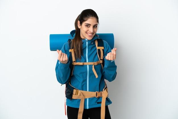 Jonge bergbeklimmer met een grote rugzak over geïsoleerde achtergrond die geldgebaar maakt