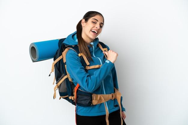 Jonge bergbeklimmer met een grote rugzak over geïsoleerde achtergrond trots en zelfvoldaan