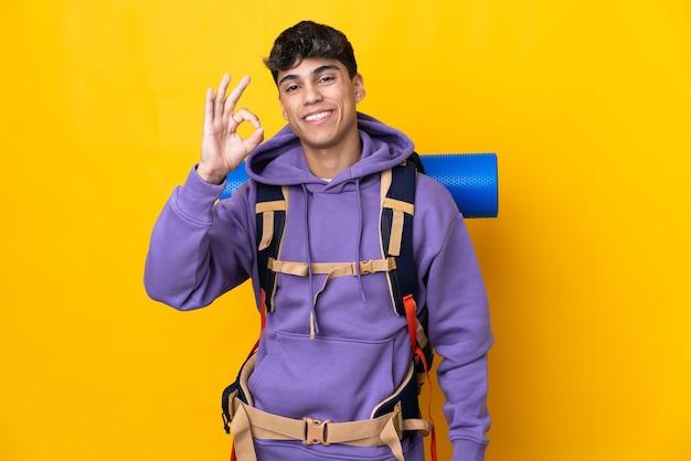 Jonge bergbeklimmer met een grote rugzak over geïsoleerde gele muur die ok teken met vingers toont