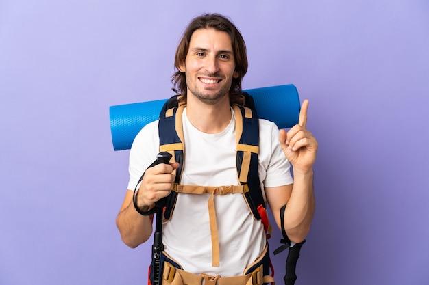 Jonge bergbeklimmer met een grote rugzak over geïsoleerde muur die en een vinger opheft als teken van het beste