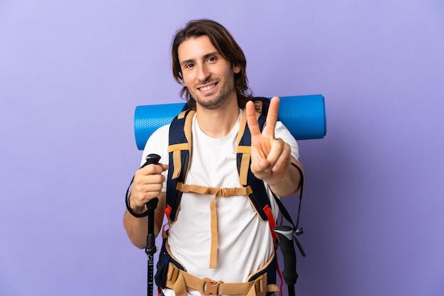 Jonge bergbeklimmer met een grote rugzak over geïsoleerde muur die en overwinningsteken glimlacht toont