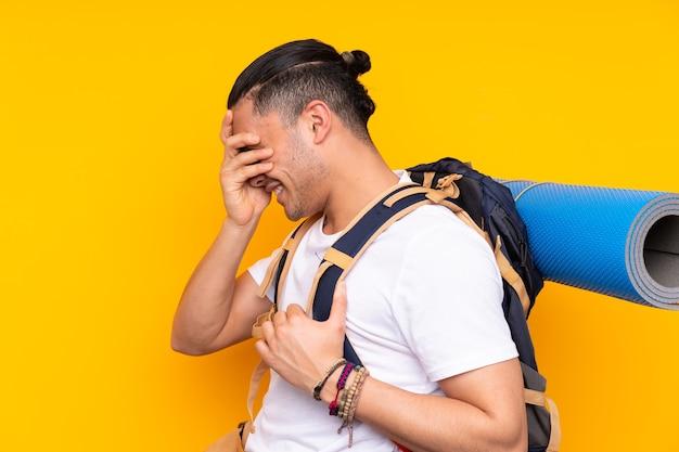 Jonge bergbeklimmer met een grote rugzak over geïsoleerde muur