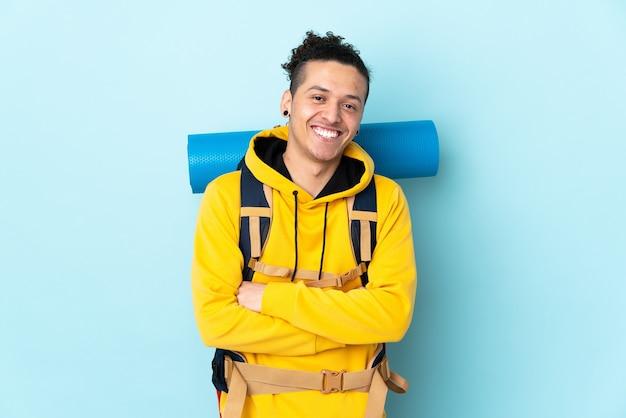 Jonge bergbeklimmer met een grote rugzak over het geïsoleerde blauwe lachen