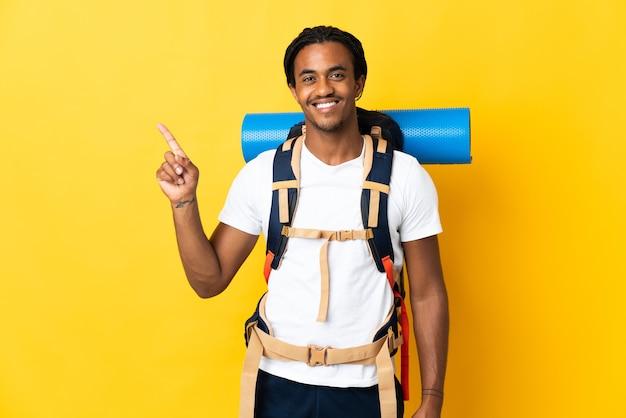 Jonge bergbeklimmer met vlechten met een grote rugzak die op gele achtergrond wordt geïsoleerd die en een vinger opheft als teken van het beste