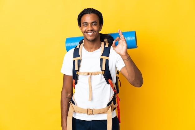 Jonge bergbeklimmer met vlechten met een grote rugzak die op gele muur wordt geïsoleerd die ok teken met vingers toont