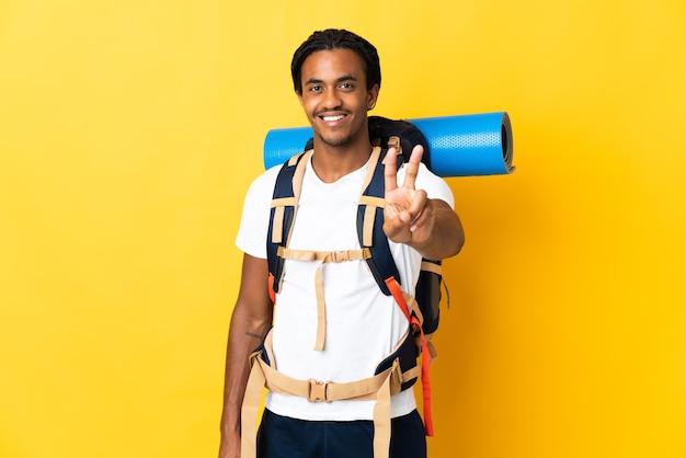Jonge bergbeklimmer met vlechten met een grote rugzak op geel glimlachend en overwinningsteken tonen