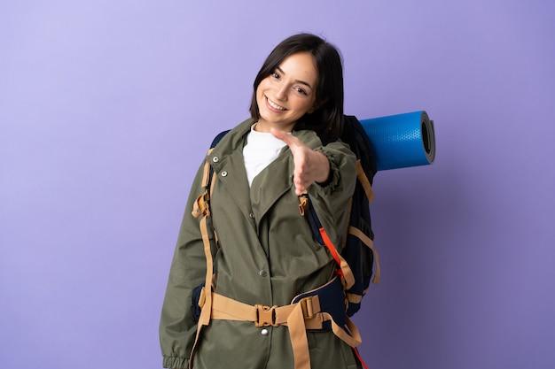 Jonge bergbeklimmer vrouw met een grote rugzak over geïsoleerde handen schudden voor het sluiten van een goede deal