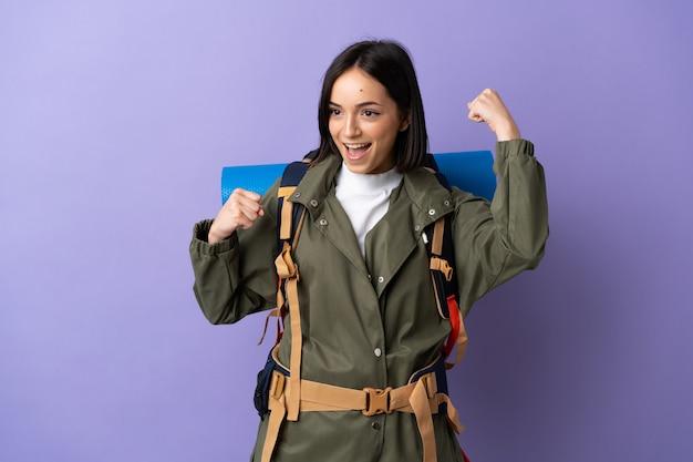 Jonge bergbeklimmer vrouw met een grote rugzak over geïsoleerde vieren een overwinning