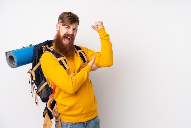Jonge bergbeklimmermens die met een grote rugzak over geïsoleerde witte muur sterk gebaar maken