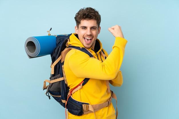 Jonge bergbeklimmermens met een grote die rugzak op blauwe muur wordt geïsoleerd die sterk gebaar maken