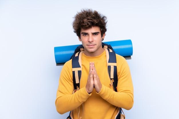 Jonge bergbeklimmermens met een grote rugzak over geïsoleerde muur