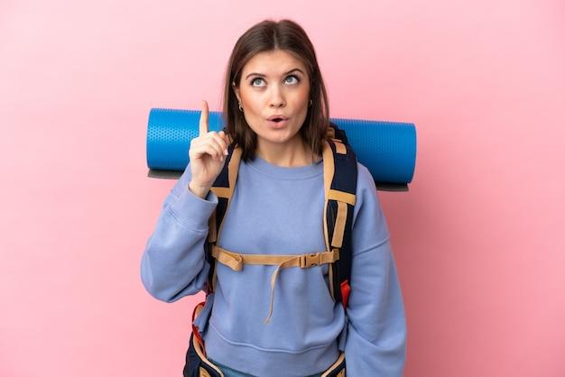 Jonge bergbeklimmervrouw met een grote geïsoleerde rugzak die de oplossing wil realiseren terwijl ze een vinger opheft Premium Foto