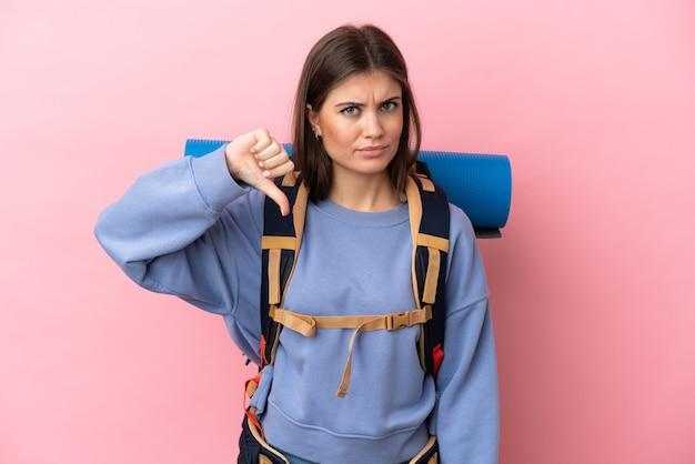 Jonge bergbeklimmervrouw met een grote geïsoleerde rugzak die duim omlaag toont met negatieve uitdrukking