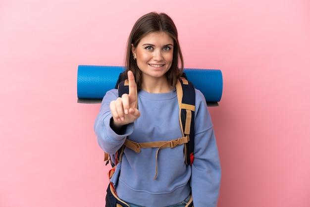 Jonge bergbeklimmervrouw met een grote geïsoleerde rugzak die een vinger toont en opheft