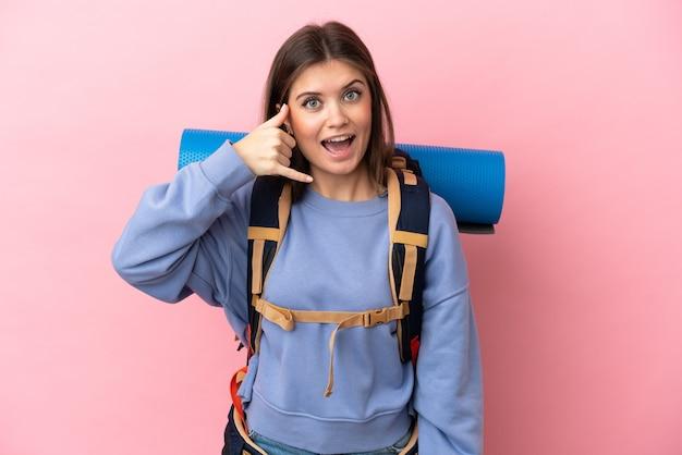 Jonge bergbeklimmervrouw met een grote geïsoleerde rugzak die telefoongebaar maakt. bel me terug teken